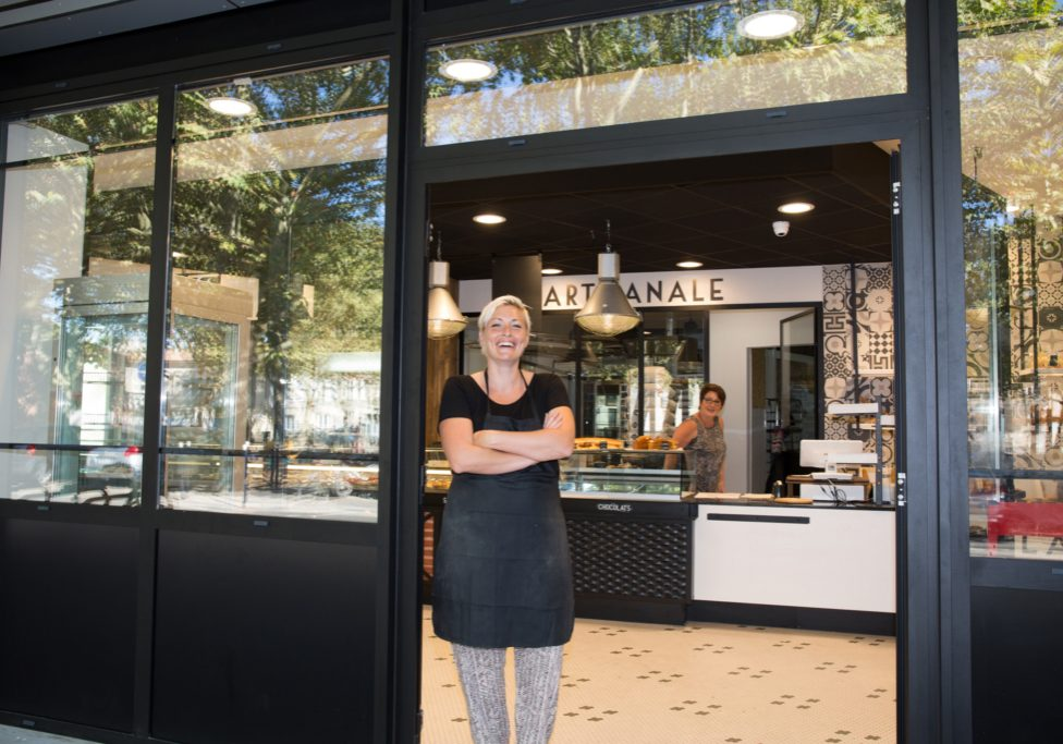 Portrait Of Confident Waitress With Arms Crossed Standing In Bakery